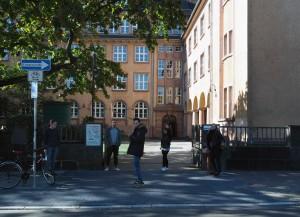 Schulgebäude und großer Hof mit Sportbelag und -markierung von der Georg-Speyer-Straße aus gesehen.
